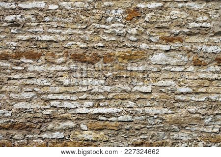 Ancient Brownish Weather Damaged Limestone Wall Background..