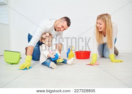 A Happy Family Is Washing The Floor Against A White Wall.