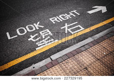 Look Right. Caution Road Marking For Pedestrians Shows Direction Of Approaching Traffic In Hong Kong