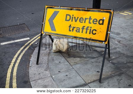 Diverted Traffic. Yellow Road Sign Stands On Street Of London City