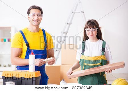 Man explaining woman woodworking tips in wood workshop