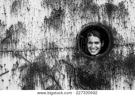 Portrait of a young woman in a round window in a rusty iron wall. Black-and-white photo.