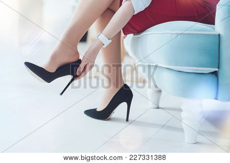 Feeling Much Better. Close Up Of A Career Woman Relaxing On A Comfortable Chair And Unshoesing Herse