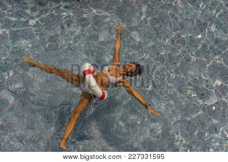 Sexy woman at the swimming pool with a  buoy