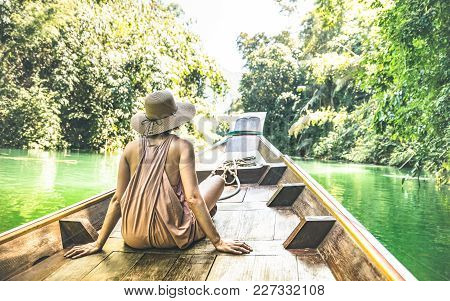 Young woman traveler on longtail boat trip at island hopping in Cheow Lan Lake - Wanderlust and travel concept with adventure girl tourist wanderer on excursion in Thailand - Warm greenish filter poster