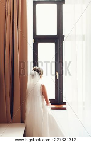 Bride In Wedding Dress Standing By Window In Room Looking Out With Back To Camera.