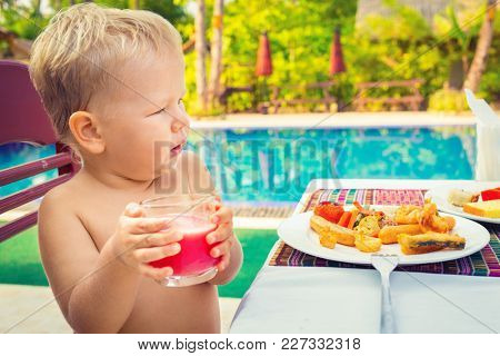 Child has a breakfast near a swimming pool