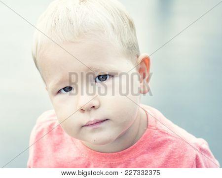 Boy lookind at camera. High key portrait