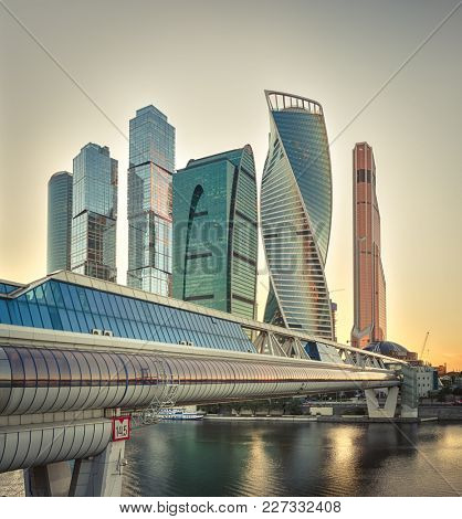 Moscow City at sunset. Moscow International Business Centre skyline at golden hour with Bagration Bridge and Moskva river in foreground