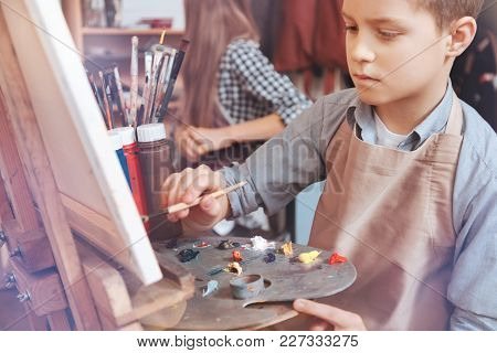 Painting Is Lifefor Me. Pensive Boy Sitting At An Easel And Looking On A Canvas While Painting With