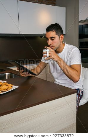 Young Man Having Breakfast In The Kitchen And Looking At The Tablet