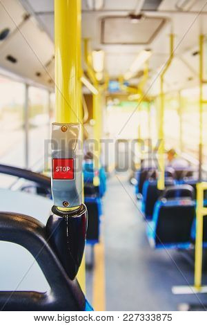 Red Button Stop On The Bus. Bus With Yellow Handrails And Blue Seats. Photo With The Sun Effect, Gla