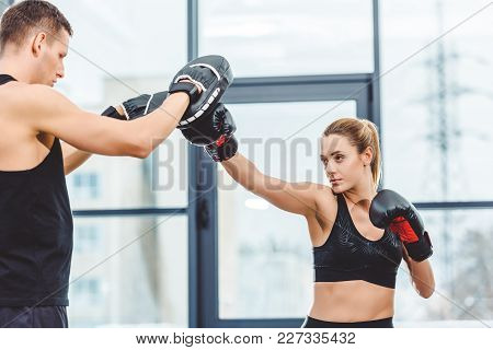 Cropped Shot Of Young Sporty Woman Boxing With Trainer In Gym