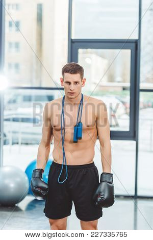 Young Muscular Sportsman In Boxing Gloves With Skipping Rope Looking At Camera In Gym