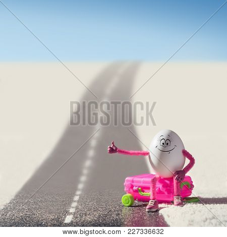Funny Egg Girl Hitchhiking On A Road In A Desert. Travel Concept.