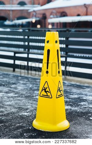 Slippery Icon On Yellow Plastic Alerts About Hazard On Road. Caution Wet Warning Sign. Danger On Roa