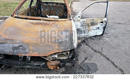 Abandoned Rusty Burned Out Car On The Street.