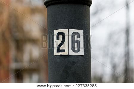 The Black Number Twenty Six On A White Background Attached To A Metal Pole