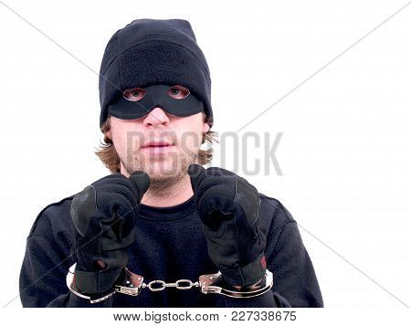 A Masked Criminal Handcuffed Isolated On White.