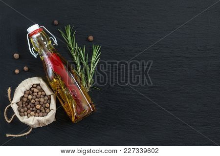 Rosemary Bunch, Olive Oil With Pepper And Spices And Fragrant Pepper On Black Stone Surface. Top Vie