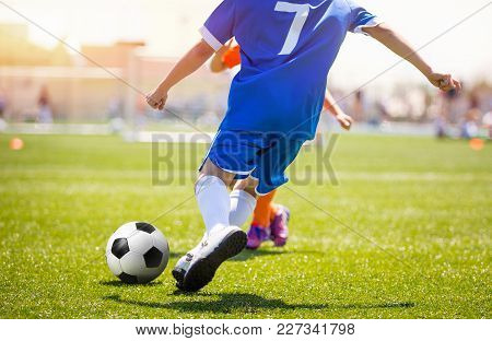 Football Player Running The Ball And Kicking Towards Opponents Goal. Soccer Stadium In The Backgroun