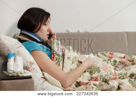 Sick Woman Lying In Bed At Home Talking On The Phone