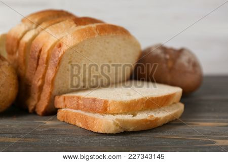 Fresh sliced bread and buns on wooden table
