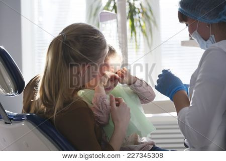 Little Child With Mommy In Stomatology Chair - Girl Is Crying, Close Up