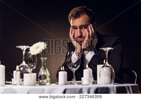 upset handsome man waiting for romantic date in restaurant poster
