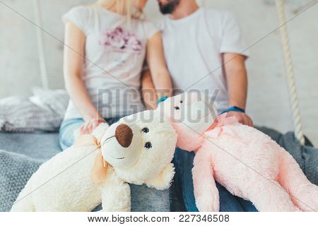 Young Beautiful Couple Sitting On The Bed With Teddy Bears In Hands