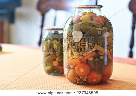 Preserved Vegetables In Two Glass Jars On The Home Kitchen Table
