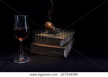 Evening Still Life Scene Of Smoking Pipe, Glass Of Scotch Whisky And Old Books Against Black Backgro