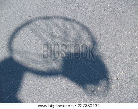 A Shadow Of A Basketball And Hoop.