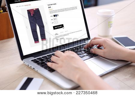 People Buying Blue Navy Jeans On E-commerce Website With Smart Phone, Credit Card And Coffee On Wood