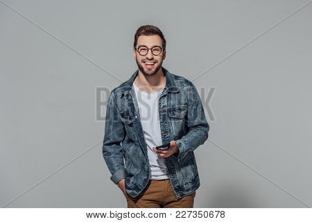 Cheerful Young Man Holding Smartphone And Smiling At Camera Isolated On Grey