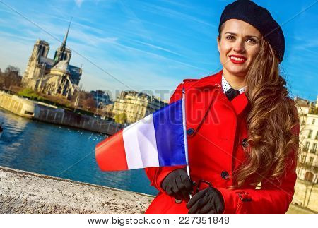 Bright In Paris. Elegant Traveller Woman In Red Trench Coat On Embankment In Paris, France With Fren