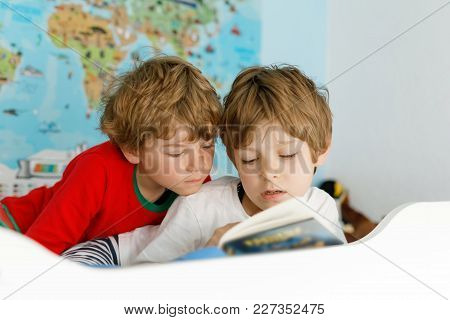 Two Little Kids Boys In Pajamas Reading A Book In Bed. Excited Siblings In Nightwear. One Brother Bo