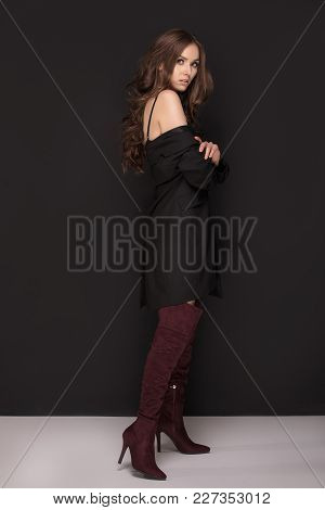 Smiling Young Beautiful Woman Posing In Fashionable Clothes, Looking At Camera. Yellow Background.