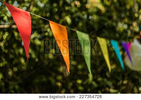 Colorful Paper Bunting Flags And Balloons Hanging For Trees At A Summer Party