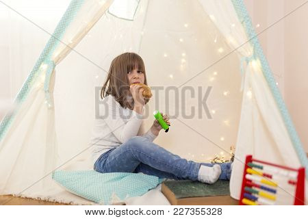 Little Girl Playing In A Tent In Her Play Room, Holding A Flashlight And Eating Croissant For Breakf