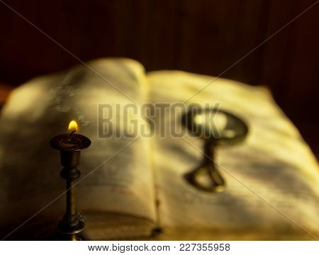 The Candle Fades With Smoke Over The Defocused Old Book With A Magnifying Glass Illuminated By The D