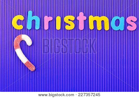 A Red And White Striped Candy Cane With The Word Christmas On A Blue Background