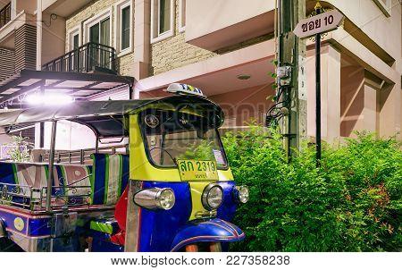 Bangkok, Thailand - February 18, 2018: Thai Taxi Tuktuk Parks Next To A Street Sign That Reads