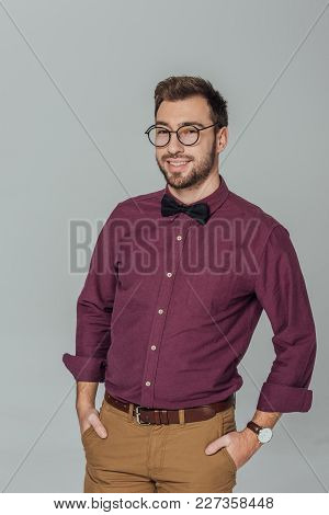 Stylish Young Man In Eyeglasses Standing With Hands In Pockets And Smiling At Camera Isolated On Gre
