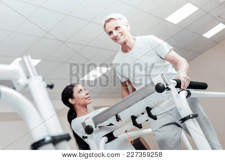 Training. Happy Old Grey-haired Man Smiling And Exercising On A Training Device And A Smiling Dark-h