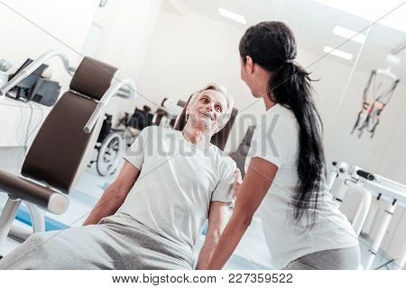 Time To Exercise. Vigorous Old Grey-haired Man Smiling And Exercising And A Dark-haired Dark-eyed Wo