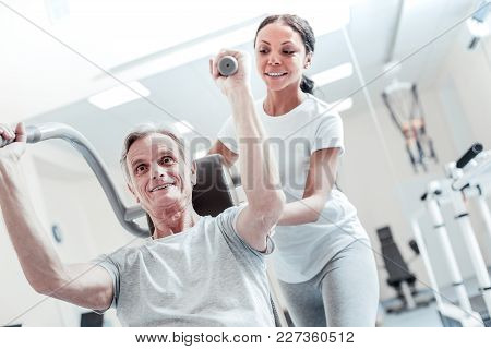 Helping Her Patient. Inspired Old Grey-haired Man Exercising On A Training Device And An Attractive