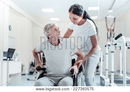 Handicapped. Concentrated Old Grey-haired Man Sitting In A Wheelchair And An Attractive Young Dark-h