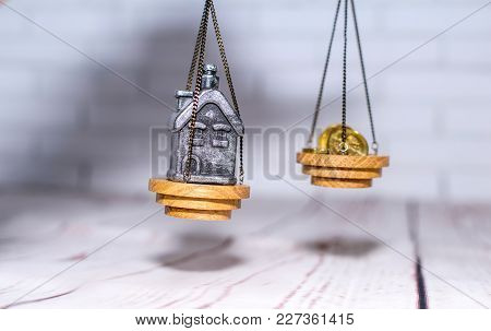 Stack Of Coins And A Small House On The Scales. The Concept Of Choice, Cash Savings And Purchase Of