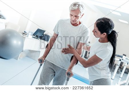 Keep Going. Attractive Concentrated Dark-haired Woman Helping A Serious Old Grey-haired Man Stand An